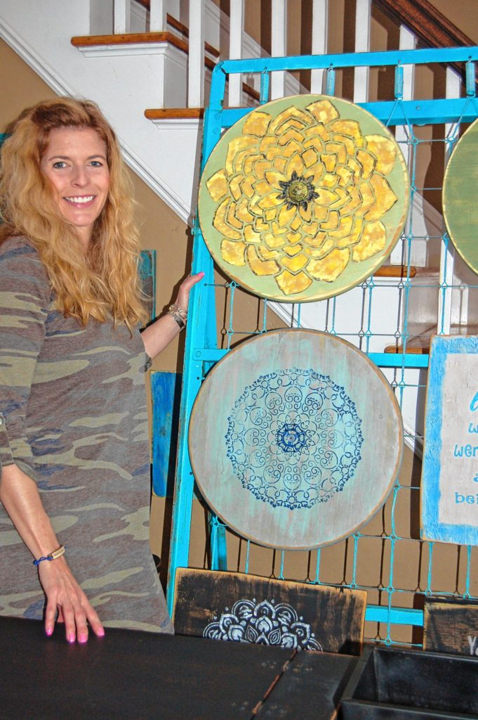 Longmeadow artist Marie Paynter stands with two of the floral wall plaques she stencils on discarded wood. On top, the center of the flower is half of an old golf ball. Below, the center is a discarded spigot handle. The display board they hang on is actually an old, metal bed frame she painted blue.