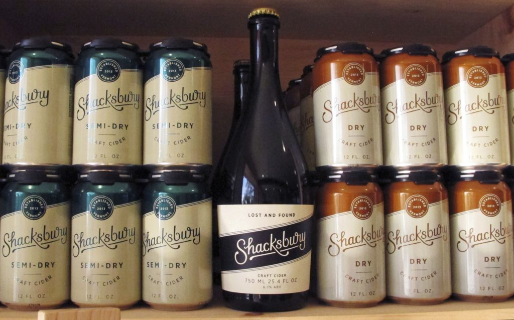 In this Oct. 4, 2017, photo, a display of Shackbury Cider's beverages sits on a shelf at the company's tasting room in Vergennes, Vt. Shacksbury Cider in Vergennes, Vermont, harvests wild apples from mountain roadsides, old farmsteads and pastures and the backyards of homes through its Lost Apple Project. It produces specialty hard ciders from the harvests and propagates its own trees from some of the best wild ones.   (AP Photo/Lisa Rathke)
