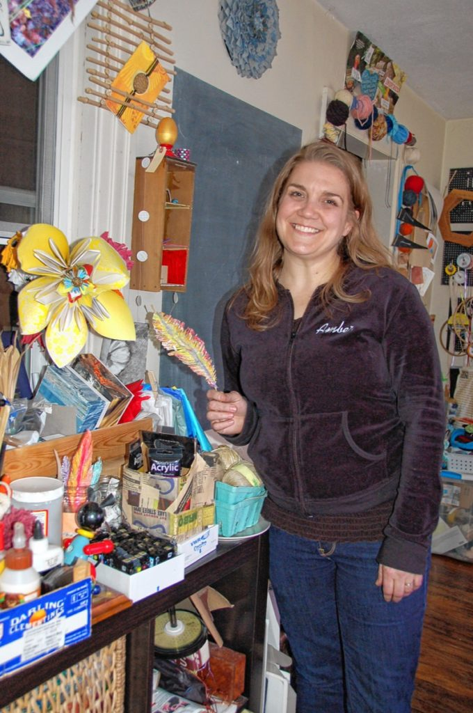 Uncycler Amber Ladley stands in her South Hadley studio holding a painted feature, which she cut from a page of a discarded library book and glued to a bamboo shoot from her yard. Also in view are a flower she made from surplus wallpaper, a hanging cardholder cut from bamboo and, above the door behind her, a decorative storage system for yarn.