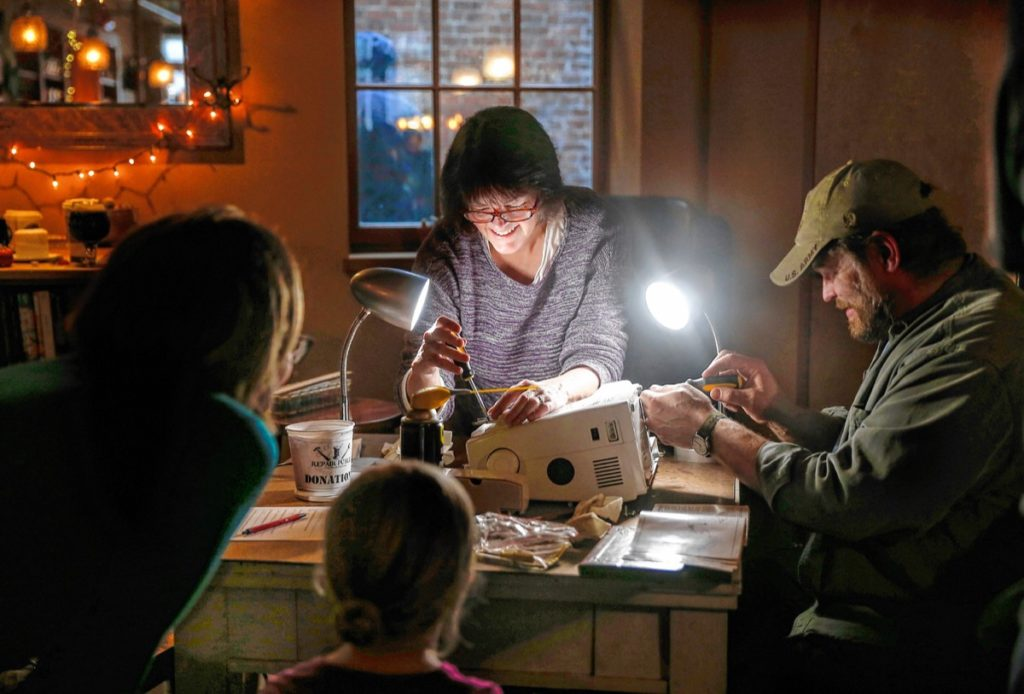 Jill Messick, center, and Karl Mosher, right, work on fixing a sewing machine while Erica Drake  looks on with her daughter Juniper Westgate, 4, during the Repair Public sponsored fix-it event at Seymour pub, on Sunday, Feb. 25, 2018 in Greenfield.