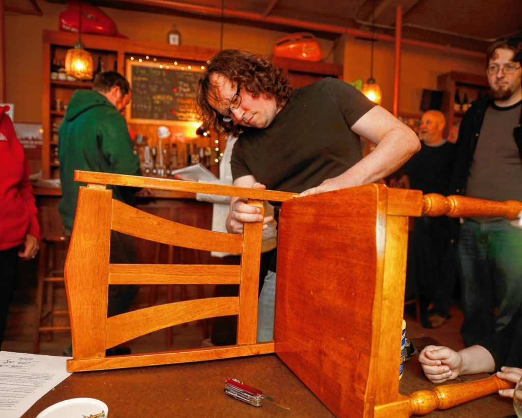 John Castorino works on fixing a wobbly chair during the Repair Public sponsored fix-it event at Seymour pub, on Sunday, Feb. 25, 2018 in Greenfield.
