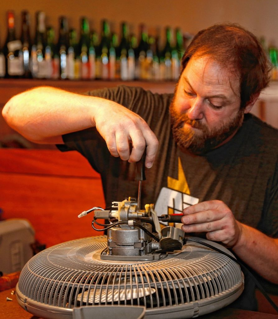 Kevin Hannon works on fixing a fan during the Repair Public sponsored fix-it event at Seymour pub, on Sunday, Feb. 25, 2018 in Greenfield.