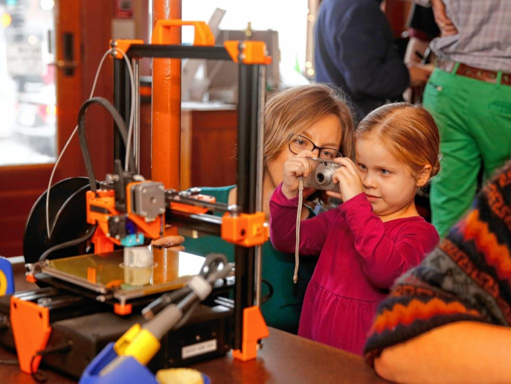 Juniper Westgate, 4, takes a picture of a 3-D printer during the Repair Public sponsored fix-it event at Seymour pub, on Sunday, Feb. 25, 2018 in Greenfield.