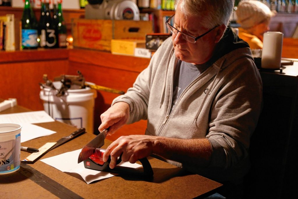 Doug Ward sharpens a set of knives during the Repair Public sponsored fix-it event at Seymour pub, on Sunday, Feb. 25, 2018 in Greenfield.