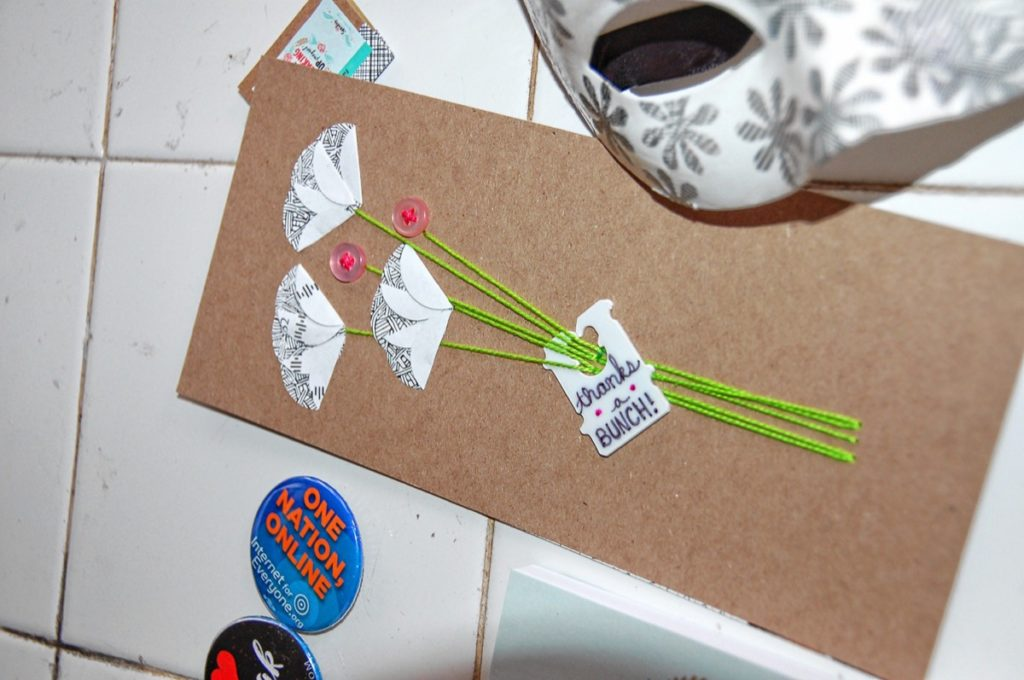This greeting card is made on recycled cardboard. The patterned flowers were cut from the crosshatching inside of security old envelopes, and the tag on the flowers is a repurposed bread bag tie.