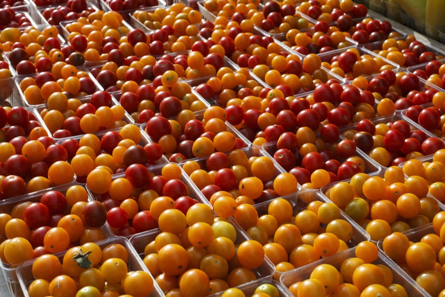 "FILE- In this July 28, 2017, file photo, cherry tomatoes are displayed for sale with summer fruits and vegetables at a farmers market in Falls Church, Va. The difference between the produce at farmers markets and supermarkets is more than ""tomayto"" versus ""tomahto."" And buying fresh fruit and vegetables at farmers markets offers opportunities to save money in ways you might not find at a grocery store. (AP Photo/J. Scott Applewhite, File)"