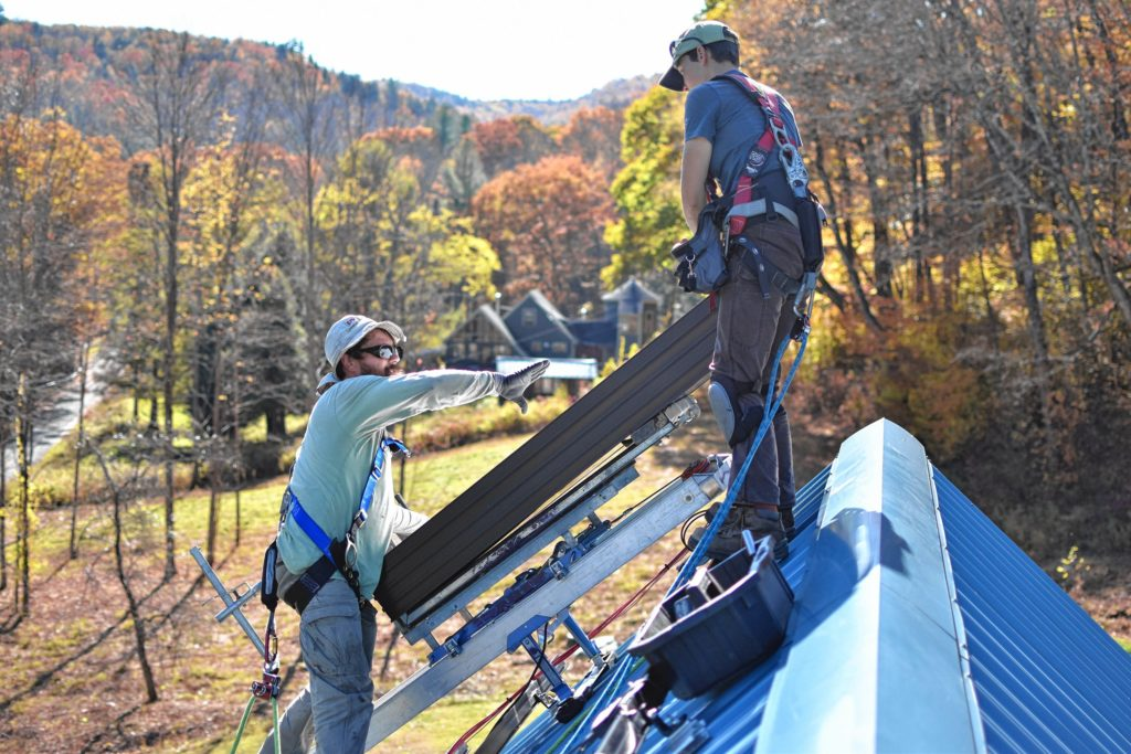 Jesse Poutasse and Emily Vail of PV Squared install solar panels atop the writer's house in Hawley last fall.