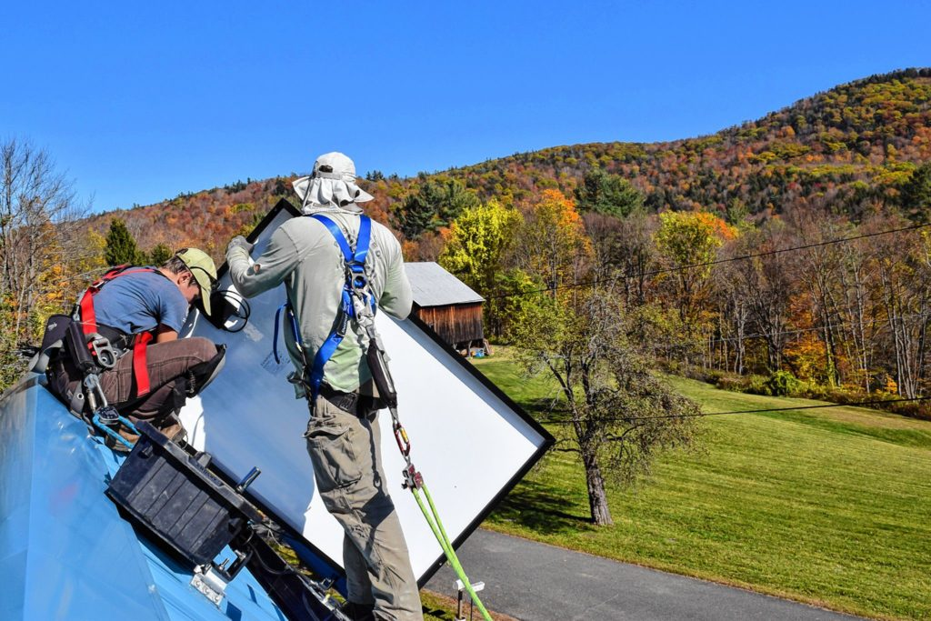 Emily Vail and Jesse Poutasse of PV Squared install solar panels atop the writer's house in Hawley last fall.