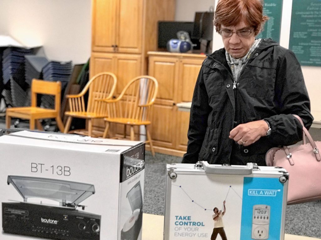 Karen Drude of Southwick looks over a Kill-a-Watt reader in the Southwick Public Library of Things. The device, which reads how much energy different home appliances use, is the kind of thing that's extremely useful, but that people tend only to need to use once.