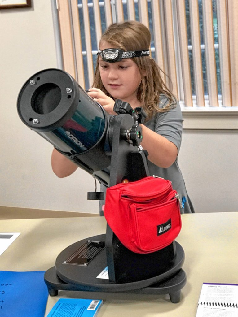 Eight-year-old Harper Bradbury of Southwick tries out her public library's Orion Starblast 4.5 telescope, which is available for loan to patrons 18 years of age and older.
