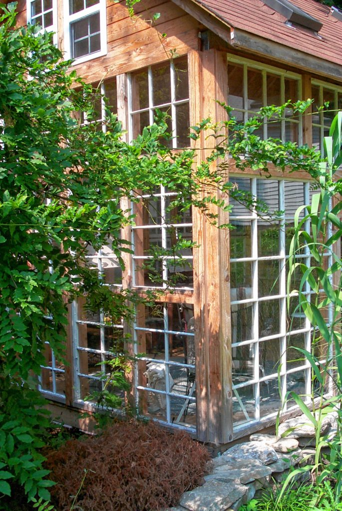 This do-it-yourself sunroom is designed around recycled storm windows and doors. Notice the windows near the peak and the roof vent to avoid summertime overheating.
