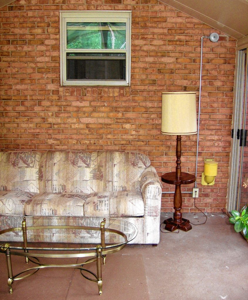 This kit sunroom is built on an existing concrete patio and has a brick house wall for thermal mass. Warm air can be drawn into the house through the window.