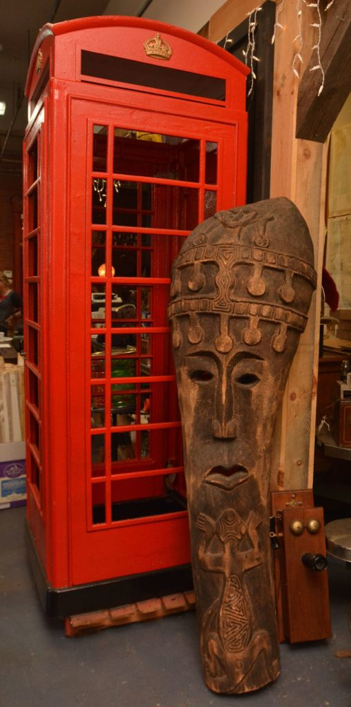 An African piece rests beside a British phone booth from the 1940's at Castle Architectural Salvage in Northampton.