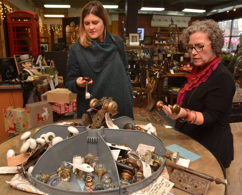 Emily Estes, left, an architect and interior designer, and Amy Woolf, an interior designer, look at vintage doorknobs at Castle Architectural Salvage in Northampton, Thursday, Nov. 21, 2019.