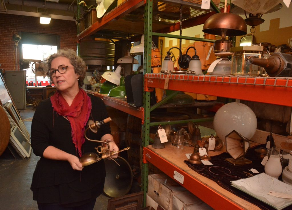 Amy Woolf, an interior designer, holds a lighting fixture at Castle Architectural Salvage.