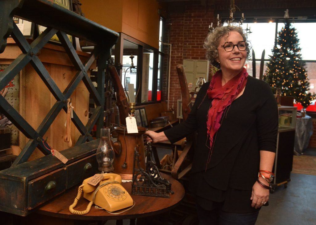 Amy Woolf, an interior designer, talks about a watering can that has been made into a lamp at Castle Architectural Salvage in Northampton, Thursday, Nov. 21, 2019.
