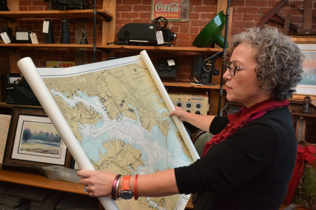 Amy Woolf, an interior designer, looks at a map at Castle Architectural Salvage in Northampton, Thursday, Nov. 21, 2019.